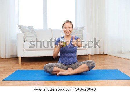 fitness, sport, people, diet and healthy lifestyle concept - happy woman with cup of smoothie sitting on mat at home and showing thumbs up - stock photo
