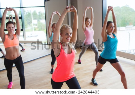 fitness, sport, people, teamwork and lifestyle concept - group of women working out in gym