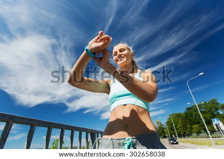 fitness, sport, people, technology and healthy lifestyle concept - smiling young woman with heart rate watch and earphones exercising outdoors - stock photo