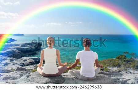 fitness, sport, people, yoga and lifestyle concept - happy couple meditating in lotus pose on summer beach from back - stock photo