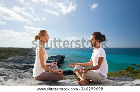 fitness, sport, people, yoga and lifestyle concept - happy couple meditating in lotus pose on summer beach - stock photo