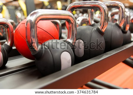 fitness, sport, sports equipment, weightlifting and bodybuilding concept - close up of kettlebells and medicine ball in gym - stock photo