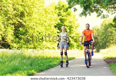 fitness, sport, summer, people and healthy lifestyle concept - happy couple with rollerskates and bicycle riding outdoors at summer