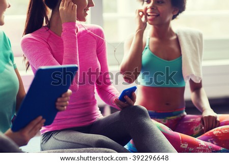 fitness, sport, technology and lifestyle concept - close up of happy women with smartphone, earphones and tablet pc computer listening to music in gym - stock photo