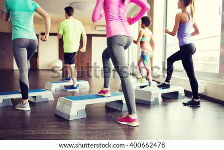 fitness, sport, training, aerobics and people concept - close up of people working out with steppers in gym from back - stock photo
