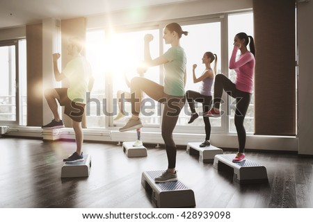 fitness, sport, training, aerobics and people concept - group of people working out with steppers in gym - stock photo