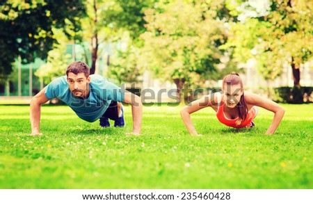 fitness, sport, training and lifestyle concept - couple doing push-ups outdoors - stock photo