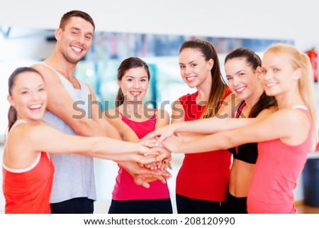 fitness, sport, training and lifestyle concept - group of happy people in the gym celebrating victory