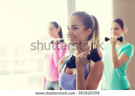 fitness, sport, training and lifestyle concept - group of happy women with dumbbells flexing muscles in gym - stock photo