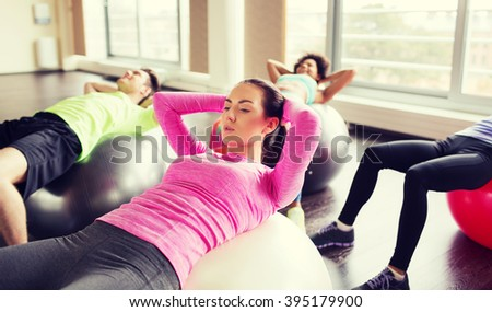 fitness, sport, training and lifestyle concept - group of people flexing abdominal muscles on fitball in gym - stock photo