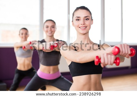 Fitness, sport, training and lifestyle concept. Group of smiling women are stretching in gym with dumbbells. - stock photo