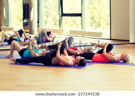 fitness, sport, training and lifestyle concept - group of women stretching in gym - stock photo