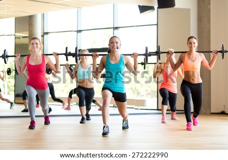 fitness, sport, training and lifestyle concept - group of women with barbells in gym - stock photo