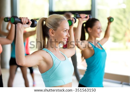 fitness, sport, training and lifestyle concept - group of women with dumbbells in gym - stock photo