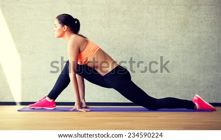 fitness, sport, training and lifestyle concept - smiling woman stretching leg on mat in gym - stock photo