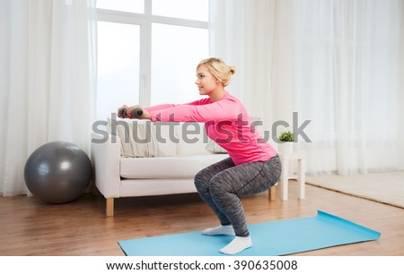 fitness, sport, training and lifestyle concept - smiling woman with dumbbells exercising and doing squats at home - stock photo