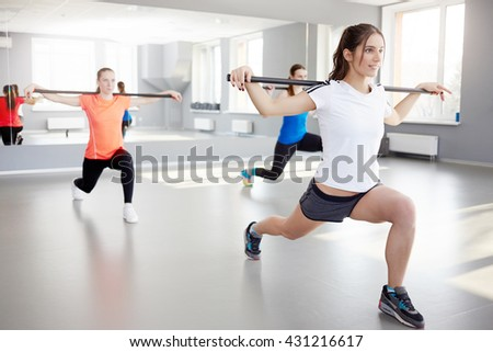 fitness, sport, training and lifestyle concept. Sporty young women exercising at fitness studio. pilates, bar