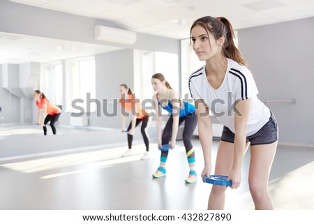 fitness, sport, training and lifestyle concept. Sporty young women exercising at fitness studio. pilates, weights plates - stock photo
