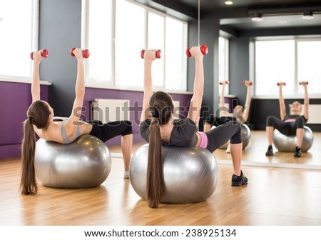 Fitness, sport, training and lifestyle concept - two smiling women with exercise balls and dumbbells in gym.