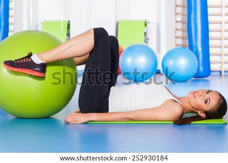 fitness, sport, training and lifestyle concept - woman stretching and doing physical exercises  with big green fitness ball in gym. - stock photo