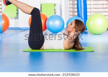fitness, sport, training and lifestyle concept - woman stretching and doing physical exercises  on mat in gym.