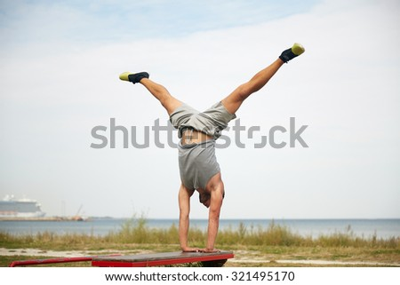 fitness, sport, training and lifestyle concept - young man exercising on bench outdoors