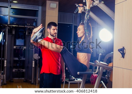 fitness, sport, training and people concept - Personal trainer helping woman working with abdominal muscles press on the horizontal bar. - stock photo
