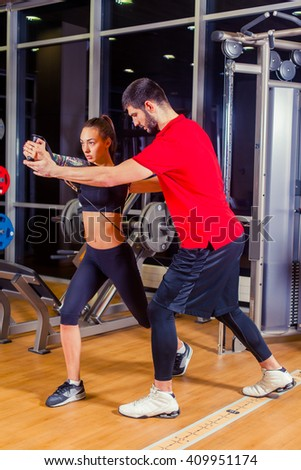 fitness, sport, training and people concept - Personal trainer helping woman working with in gym - stock photo