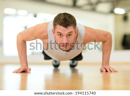 fitness, sport, training, gym and lifestyle concept - concentrated man doing push-ups in the gym - stock photo