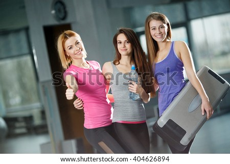 fitness, sport, training, gym and lifestyle concept - group of happy people in the gym with water bottle and sport inventory. Happy group of fit people at the gym - stock photo