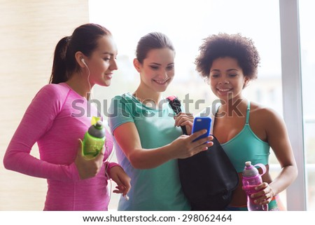 fitness, sport, training, gym and lifestyle concept - group of happy women with bottles and smartphone in gym - stock photo