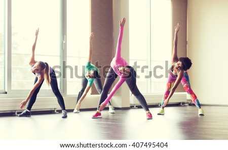fitness, sport, training, gym and lifestyle concept - group of happy women working out and stretching in gym - stock photo