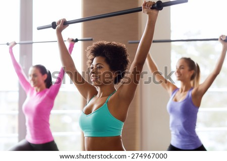 fitness, sport, training, gym and lifestyle concept - group of people exercising with bars in gym - stock photo