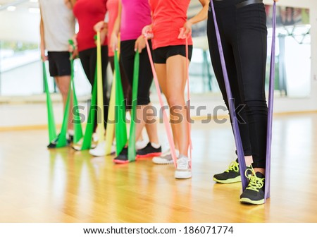 fitness, sport, training, gym and lifestyle concept - group of people with working out with rubber bands in the gym - stock photo