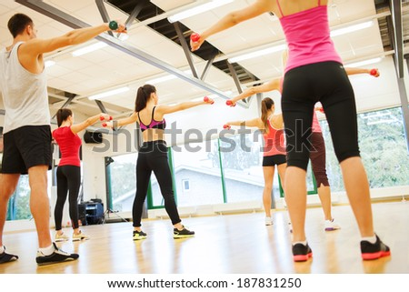 fitness, sport, training, gym and lifestyle concept - group of people working out with dumbbells in the gym from the back - stock photo
