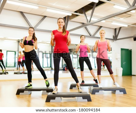 fitness, sport, training, gym and lifestyle concept - group of smiling female doing aerobics - stock photo