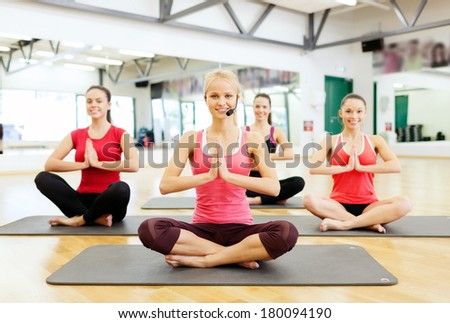 fitness, sport, training, gym and lifestyle concept - group of smiling female with trainer meditating in the gym - stock photo