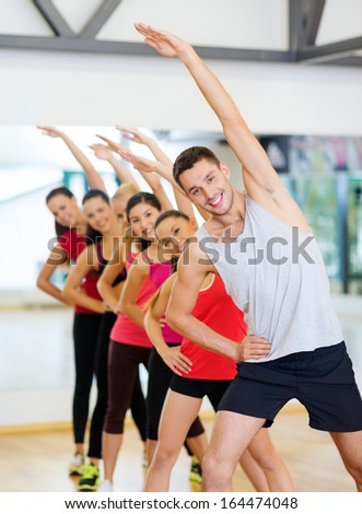 fitness, sport, training, gym and lifestyle concept - group of smiling people stretching in the gym - stock photo