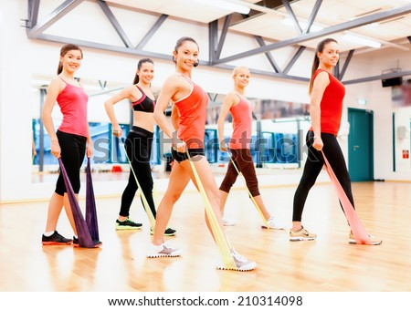 fitness, sport, training, gym and lifestyle concept - group of smiling people with instructor working out with rubber bands in the gym - stock photo