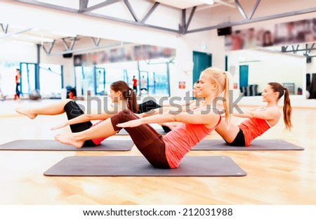 fitness, sport, training, gym and lifestyle concept - group of smiling women exercising on mats in the gym - stock photo