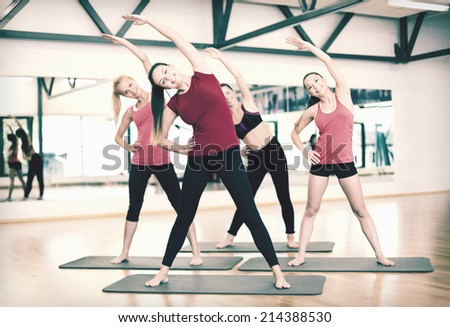 fitness, sport, training, gym and lifestyle concept - group of smiling women stretching in the gym - stock photo