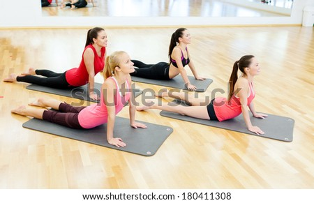 fitness, sport, training, gym and lifestyle concept - group of smiling women stretching on mats in the gym