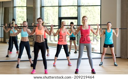 fitness, sport, training, gym and lifestyle concept - group of women with bars in gym