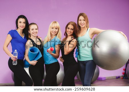 fitness, sport, training, gym and lifestyle concept - smiling group of people in gym. Portrait of three fit young women smiling in a bright exercise room.  - stock photo