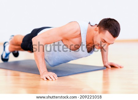 fitness, sport, training, gym and lifestyle concept - smiling man doing push-ups in the gym or at home - stock photo