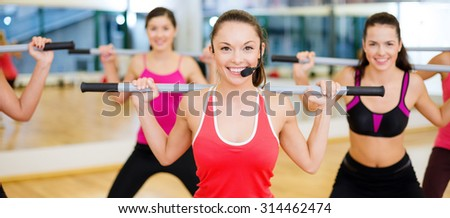 fitness, sport, training, gym and lifestyle concept - smiling trainer in front of the group of people working out with barbells in the gym - stock photo