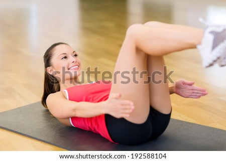 fitness, sport, training, gym and lifestyle concept - smiling woman doing exercise on mat in gym - stock photo