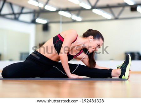 fitness, sport, training, gym and lifestyle concept - smiling woman stretching on mat in the gym