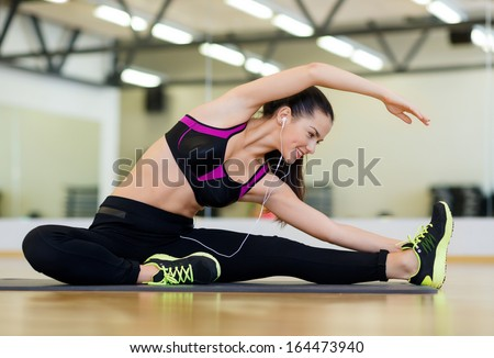 fitness, sport, training, gym and lifestyle concept - stretching young woman with earphones in the gym - stock photo