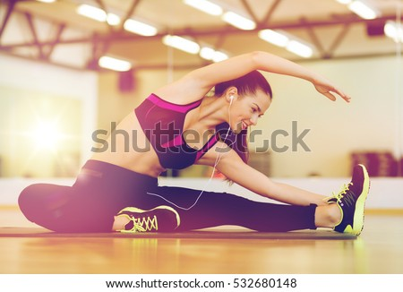 fitness, sport, training, gym and lifestyle concept - stretching young woman with earphones in the gym